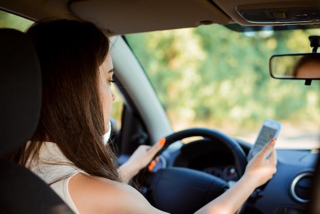 Chica estudiante conduciendo un coche y enviando mensajes de texto en el camino