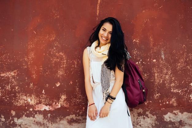 Chica estudiante confundida en vestido blanco está de pie con mochila y sonriendo