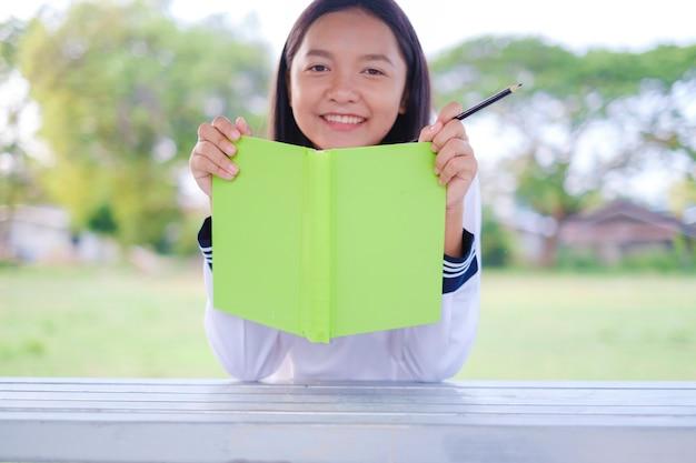 Chica estudiante con emplazamiento de libro verde en la escuela