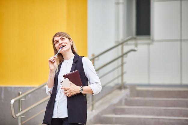 Chica estudiante se para en los escalones del edificio y sueña.