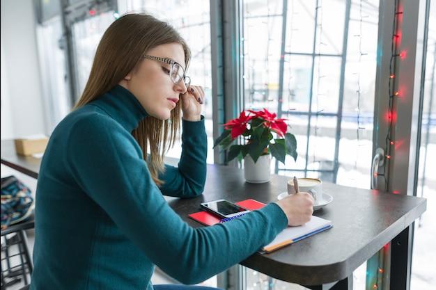 Chica estudiante estudiando en café con teléfono inteligente y portátil