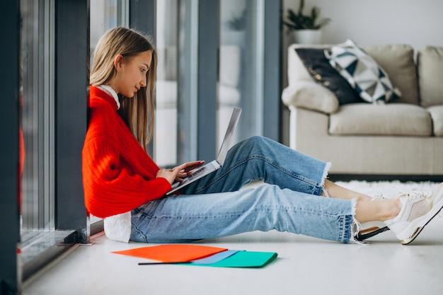 Chica estudiante estudiando en la computadora junto a la ventana