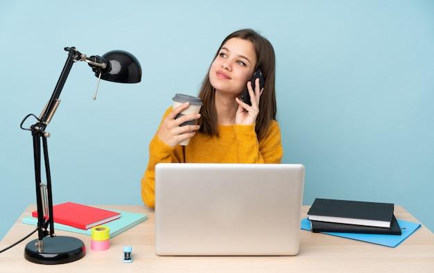 Chica estudiante estudiando en su casa aislada en la pared azul con café para llevar y un móvil
