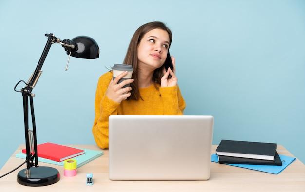 Chica estudiante estudiando en su casa en azul con café para llevar y un móvil