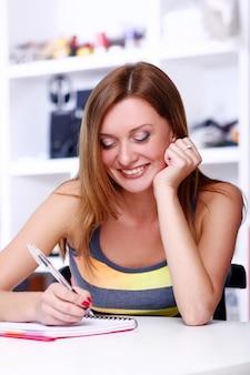Chica estudiante feliz escribiendo algo