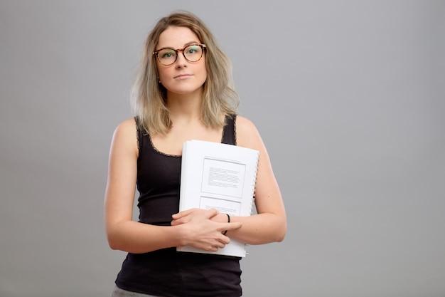 Chica estudiante con gafas sosteniendo un libro