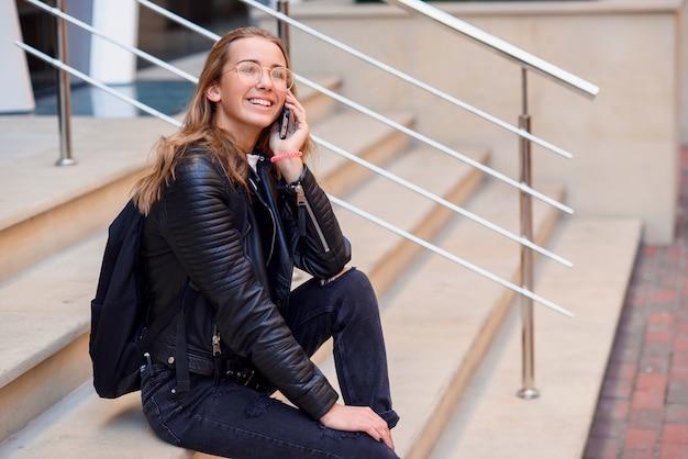 Chica estudiante hermosa alegre habla por teléfono inteligente en las escaleras en la calle, disfrutando de caminar al aire libre.