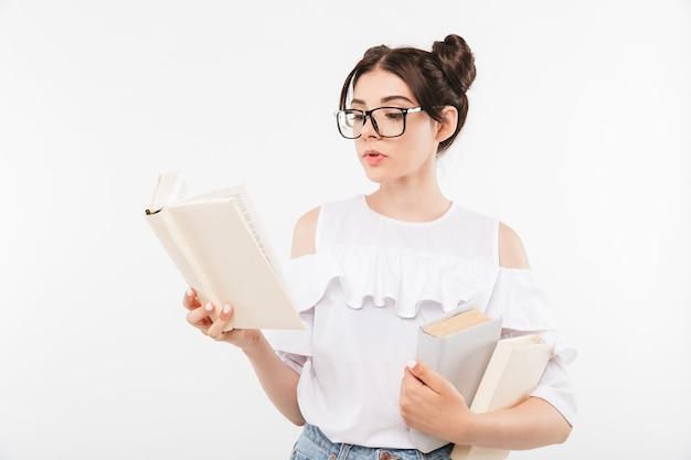Chica estudiante inteligente europea con peinado de bollos dobles y aparatos dentales estudiando y leyendo libros con interés, aislado en blanco