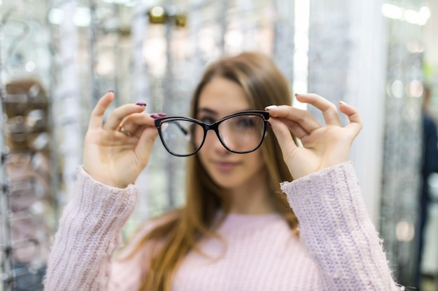 Chica estudiante joven y cuidadosa está preparándose para estudiar en la universidad y probar gafas nuevas para su apariencia perfecta en la tienda profesional