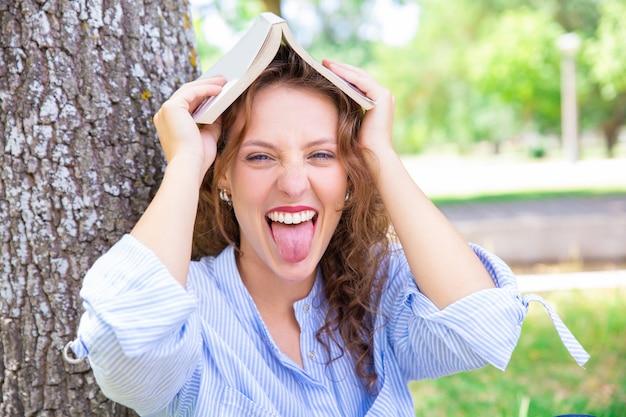 Chica estudiante juguetona divirtiéndose en el parque de verano