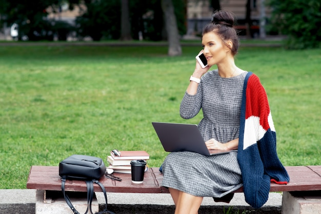 Chica estudiante con laptop está hablando por teléfono inteligente mientras está sentado en el banquillo.