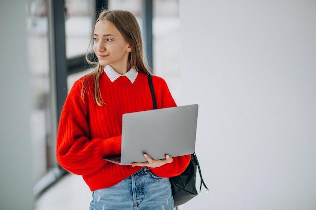 Chica estudiante con laptop de pie junto a la ventana en el pasillo