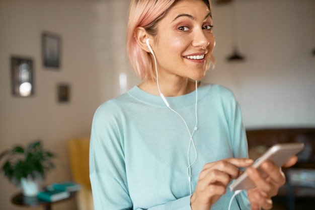 Chica estudiante linda positiva divirtiéndose en el interior después de la universidad usando auriculares mientras chatea en línea a través del chat de video en su teléfono inteligente