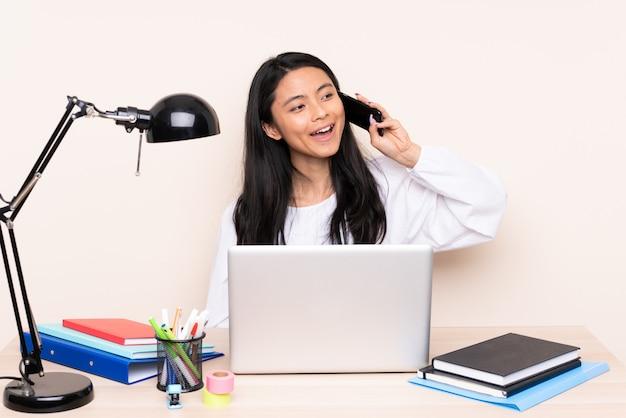 Chica estudiante en un lugar de trabajo con una computadora portátil aislada en beige manteniendo una conversación con el teléfono móvil