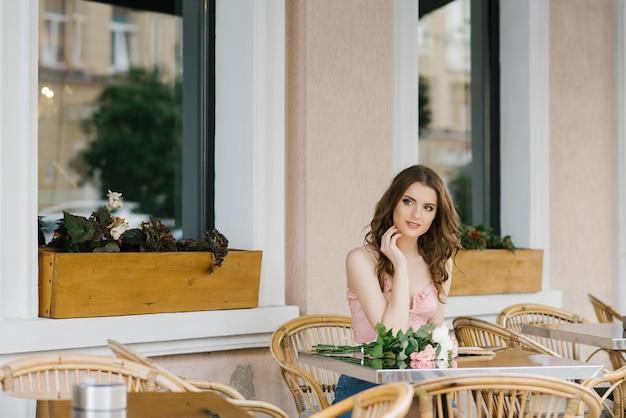 Chica estudiante de una manera romántica sentado en una mesa de café de la calle