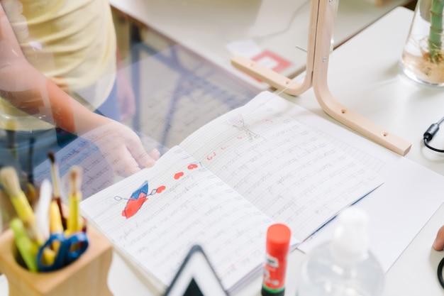 Chica estudiante con máscara entregando tareas al profesor a través de una pantalla de metacrilato durante la pandemia de covid. regreso a la escuela manteniendo la distancia social