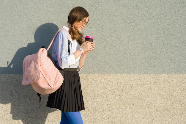 Chica estudiante con mochila escolar y vaso de bebida.
