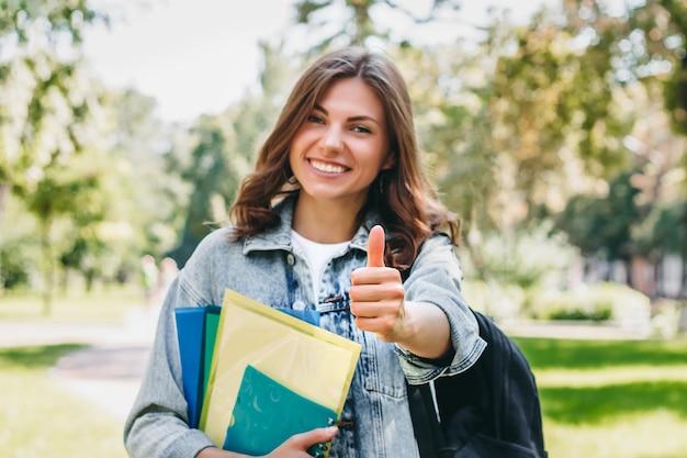 Chica estudiante muestra gesto como en el parque. la alumna aprobó con éxito el examen