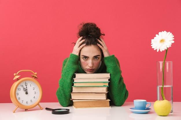 Chica estudiante nerd joven confundido sosteniendo la cabeza mientras está sentado junto a la mesa con libros