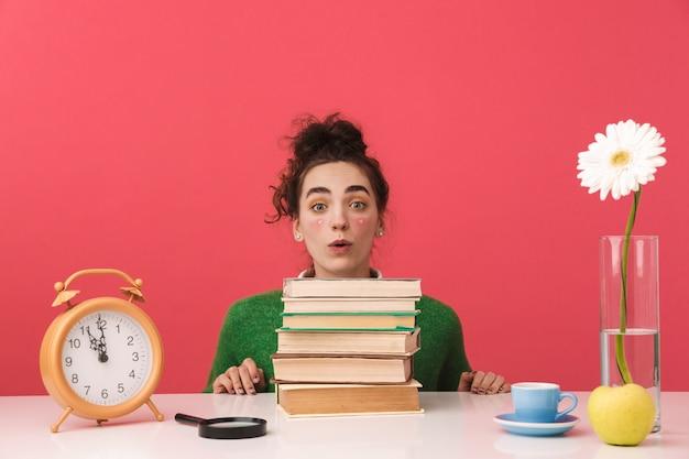 Chica estudiante nerd joven sorprendido sentado junto a la mesa con libros