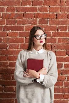 Chica estudiante de pie con libro de texto