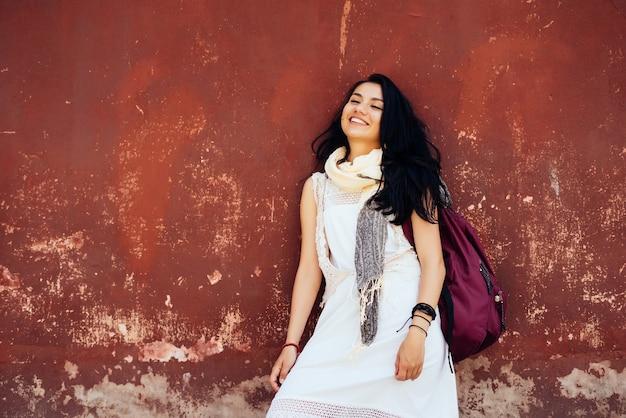 Chica estudiante riendo con vestido blanco está de pie con mochila y sonriendo, vacaciones, colegio