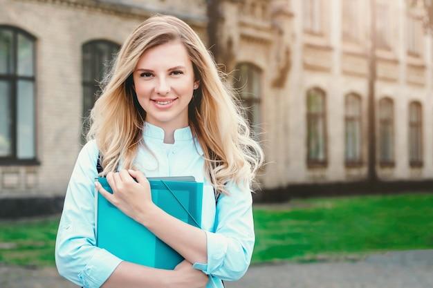 Una chica estudiante rubia está sonriendo y sosteniendo una carpeta y un cuaderno en sus manos sobre un fondo universitario