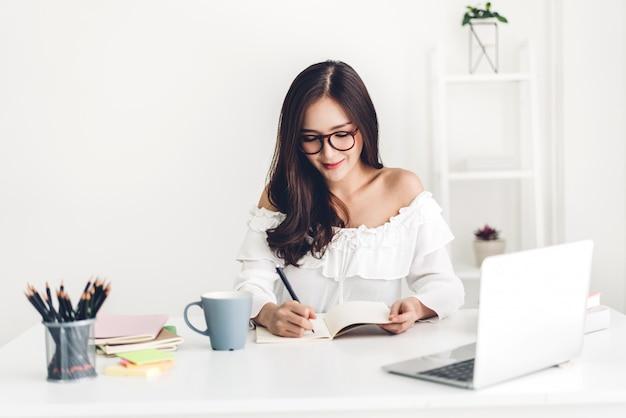 Chica estudiante sentada y estudiando y aprendiendo en línea con una computadora portátil y leyendo un libro antes del examen en casa. concepto de educación
