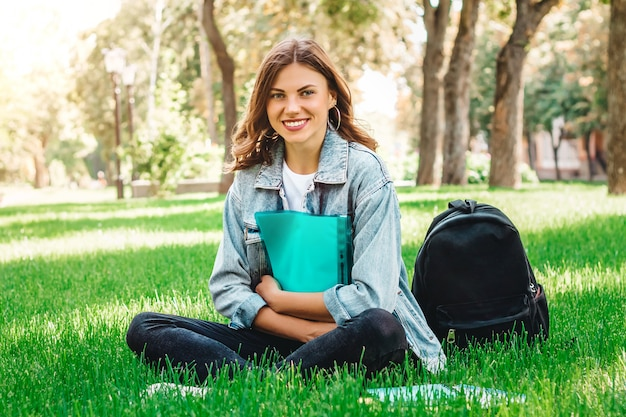 Chica estudiante sentada en el parque en el césped con libros y cuadernos