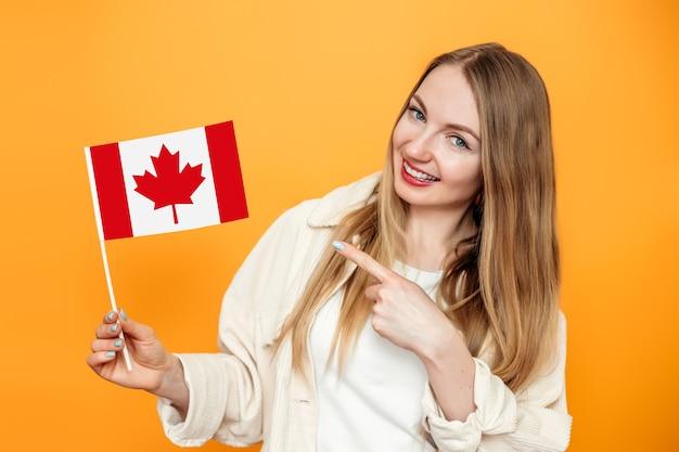 Chica estudiante sonriendo y apuntando con el dedo a la pequeña bandera de canadá