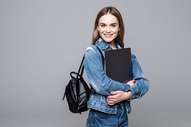Chica estudiante sonriendo a la cámara, presionando la computadora portátil contra el pecho, con mochila, lista para ir a estudios, comenzar un nuevo proyecto y sugerir nuevas ideas aisladas en la pared gris