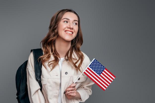 Chica estudiante sonriendo sosteniendo mochila y bandera de estados unidos aislado en una pared gris oscuro concepto de intercambio de estudiantes