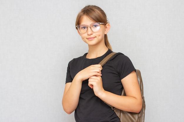 Chica estudiante sonriente vistiendo gafas y mochila escolar