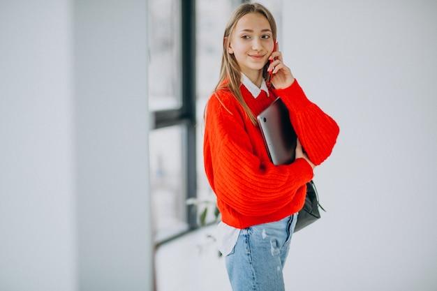 Chica estudiante sosteniendo la computadora y hablando por teléfono junto a la ventana