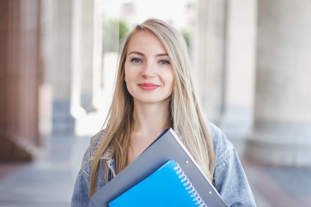Chica estudiante sosteniendo un cuaderno y sonriendo