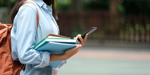 Chica estudiante sosteniendo libros y teléfono inteligente mientras camina en el fondo del campus de la escuela