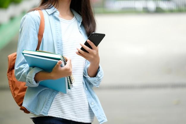 Chica estudiante sosteniendo libros y usando teléfonos inteligentes, educación en línea, comunicación tecnológica