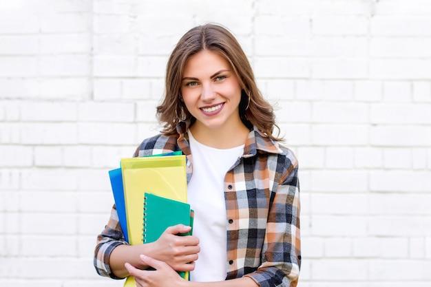 Chica estudiante sostiene carpetas y un cuaderno en sus manos y sonríe sobre un fondo de una pared de ladrillo blanco