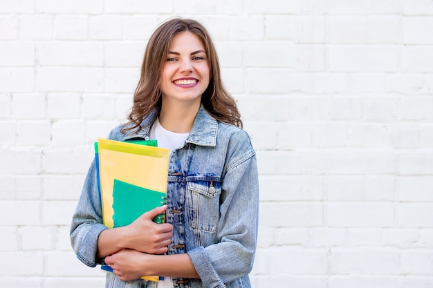 Chica estudiante tiene carpetas y un cuaderno en sus manos y sonríe sobre un fondo de una pared de ladrillo blanco, espacio de copia