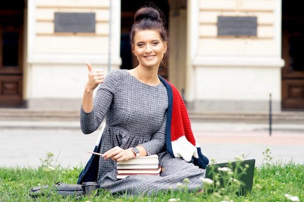 Chica de estudiantes satisfechos está mostrando el pulgar hacia arriba mientras está sentado en el césped.