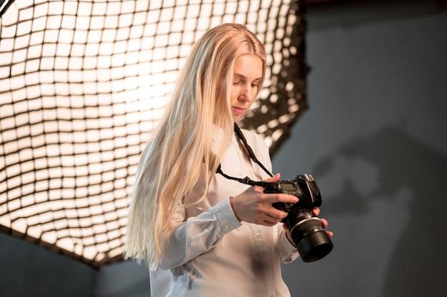 Chica en estudio usando una cámara photo