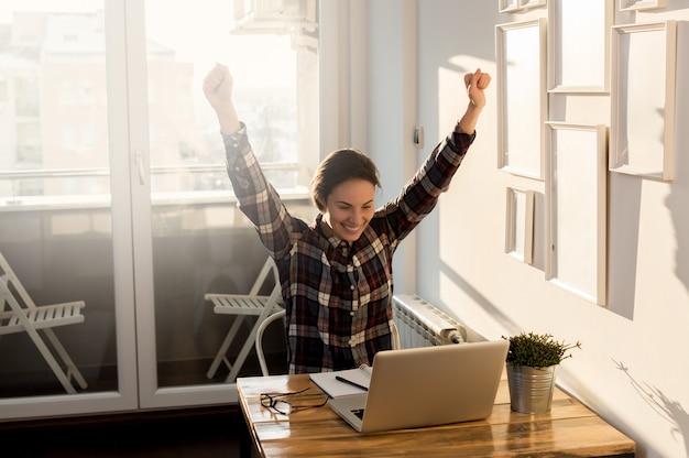 Chica eufórica en casa, mirando la pantalla de la computadora