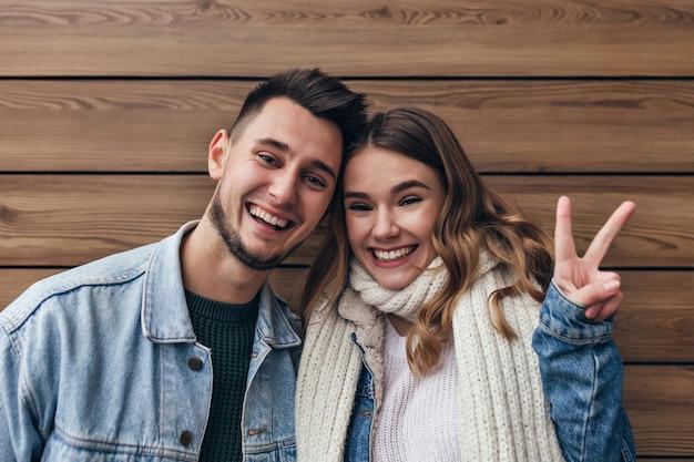 Chica europea alegre en bufanda tejida posando con el signo de la paz en la pared de madera. filmación en interiores de la risa pareja casada divirtiéndose juntos.