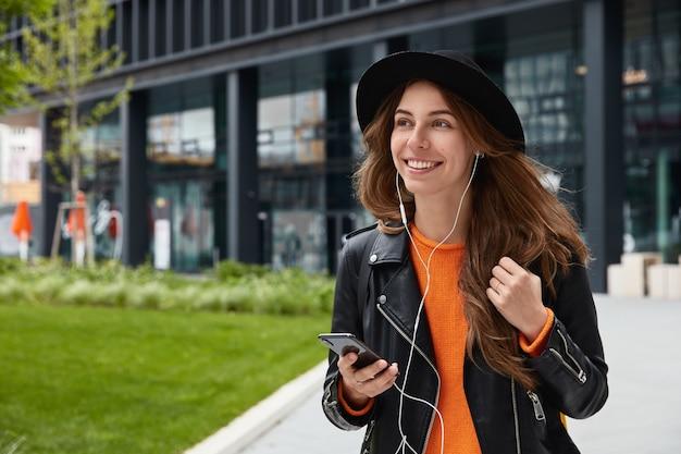 Chica europea bastante alegre en ropa de moda, camina por la metrópoli, disfruta de la canción de la lista de reproducción en línea en los auriculares
