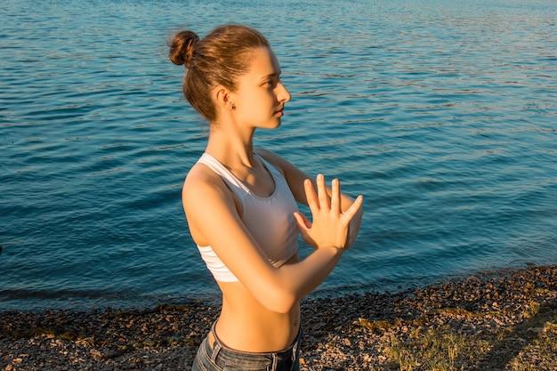 Una chica europea en un chándal ligero practica yoga en la orilla del río sobre una estera de goma para yoga