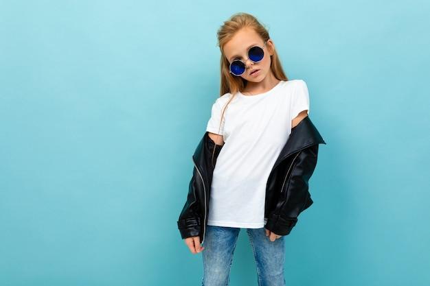 Chica europea descarada en gafas de sol con una camiseta sin mangas con maqueta sobre un fondo azul claro