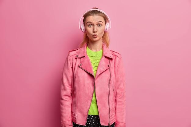 Una chica europea divertida mantiene los labios redondeados, escucha música en auriculares, elige una canción en la lista de reproducción, va camino a la escuela, se viste con una chaqueta rosa fascinante, disfruta de su cantante favorita