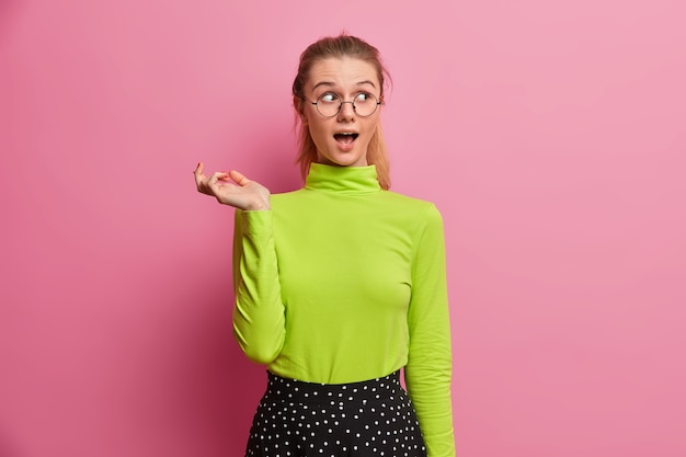 Chica europea emocionada e intrigada con la boca muy abierta, asombrada y con gran interés, mantiene la mano levantada, jadea asombrada, nota algo impresionante, usa ropa brillante