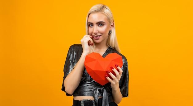 Chica europea con una figura de corazón 3d en sus manos sobre una superficie de estudio naranja. día de san valentín