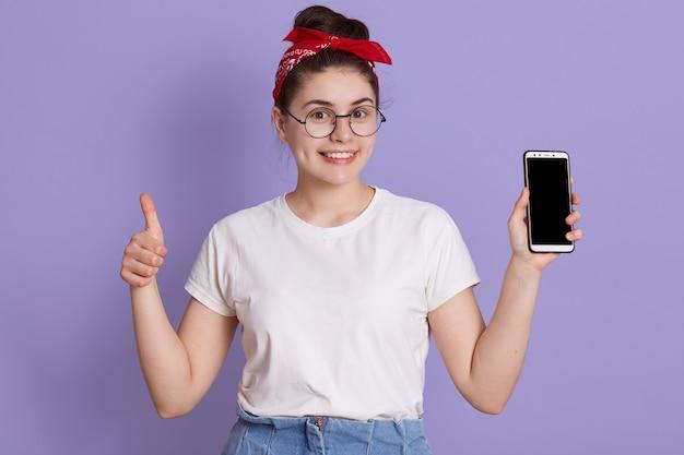 Chica europea mostrando la pantalla del teléfono móvil en blanco y mostrando el pulgar hacia arriba mientras mira feliz